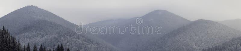 Korkad bergskedja för snö under i lager himmel arkivfoton