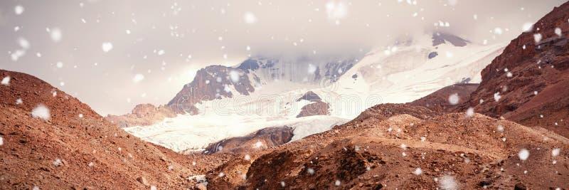 Korkade berg för snö på en solig dag arkivfoto
