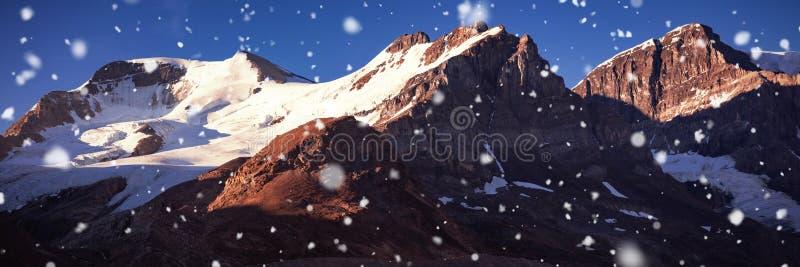 Korkat berg för snö på en solig dag arkivfoton