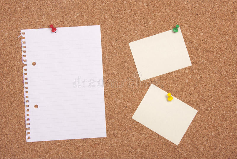 Korkbräde med anmärkningspapper arkivbild
