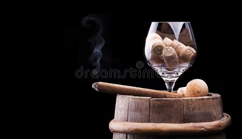 Korken im Kognak-Glas und der Zigarre auf Schwarzem lizenzfreies stockfoto