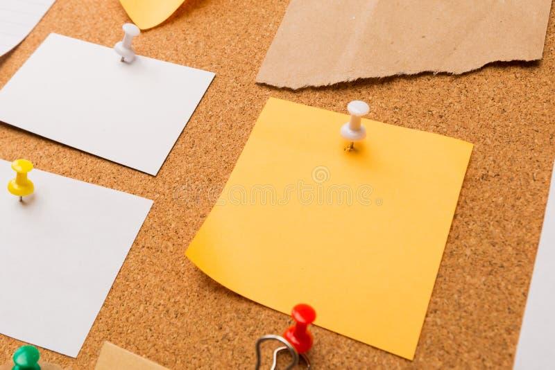 Korkenbrett mit festgesteckten farbigen leeren Anmerkungen - Bild lizenzfreie stockfotos