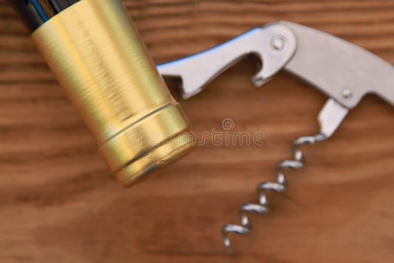 Korkenzieher und Engpass auf hölzernem Hintergrund lizenzfreies stockfoto