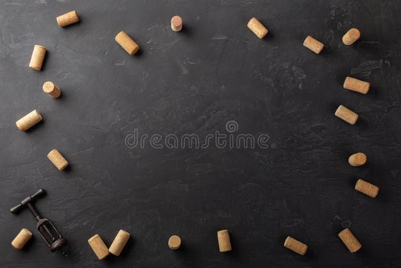 Korki i corkscrew na czarnym tle zdjęcia stock