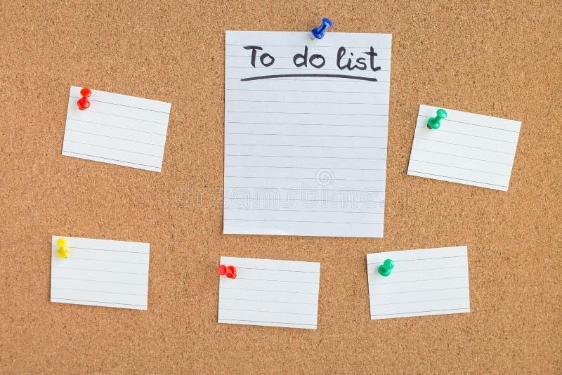 Korkminnesbräde med klämde fast tomma freder av papper, att göra listan arkivbild