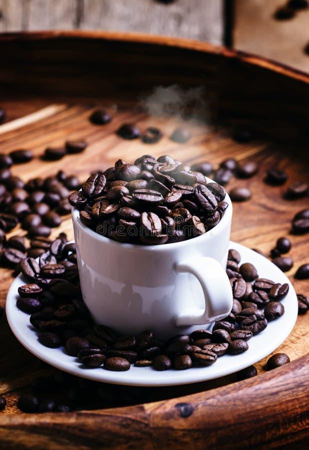 Korn av grillat kaffe i en vit kopp, tappningträbackgrou royaltyfri bild