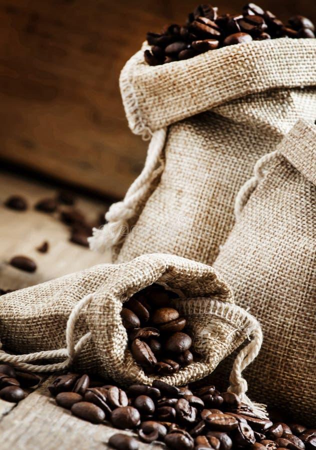 Korn av grillat kaffe i påsar på den gamla trätabellen i lantligt s royaltyfri foto