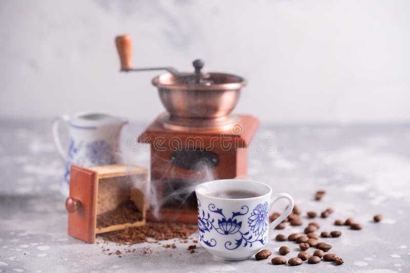 Korn av kaffe faller ut ur en tappningkaffekvarn Varmt svart kaffe i en härlig porslinkopp på tabellen En härlig com arkivfoton