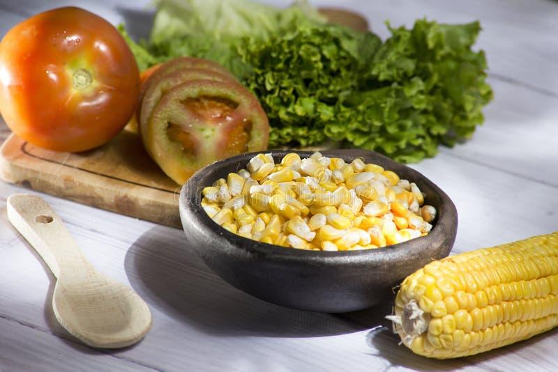 Korn av majskolven och gul havre i lergodseldfasta formen som medföljs av en läcker sallad på vit träbakgrund arkivfoton