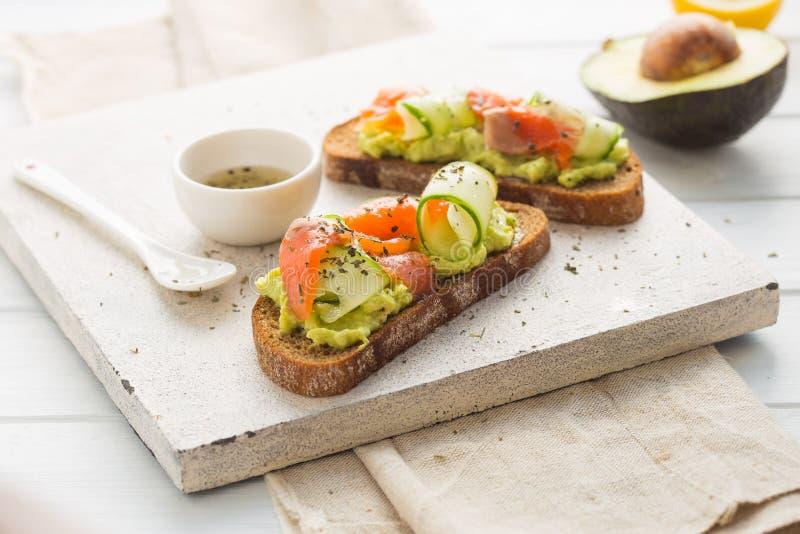 Kornbröd för öppen smörgås eller rostat brödmed laxen, vit ost, avokadot, gurkan och spenat Sunt mellanmål, sunt fett och omega royaltyfria bilder