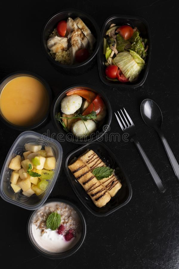 kornbröd, havremjöl, pumpasoppa med ångade grönsaker, grönsallat och exotisk fruktsallad på den svarta tabellen royaltyfria foton