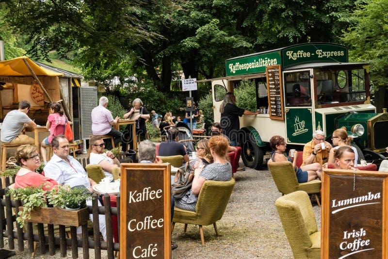 KORNELIMUENSTER, ГЕРМАНИЯ, 18-ое июня 2017 - люди в caffee улицы на исторической ярмарке Kornelimuenster на солнечный теплый день стоковые изображения