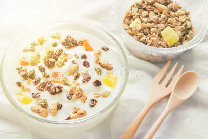 KornGranola i ett glass mjölkar flaskan och frukt på en vit torkduk i morgonen arkivfoto