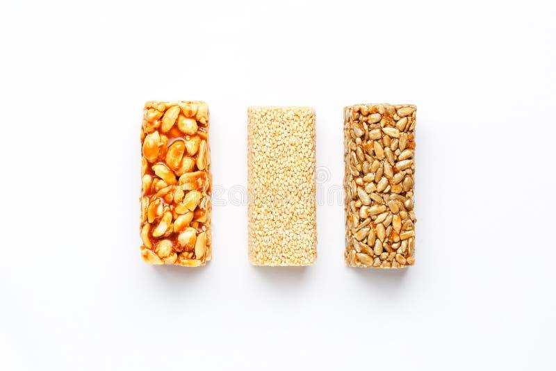 Korngranolastång med jordnötter, sesam och frö i rad på en vit bakgrund Blandade stänger för bästa sikt tre, isolat royaltyfri fotografi