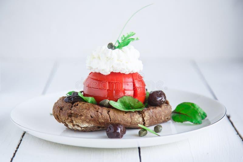 Kornskorpadakos som överträffas med fetaost, tomatkuber, olivolja och oreganon, grekisk aptitretare royaltyfri bild