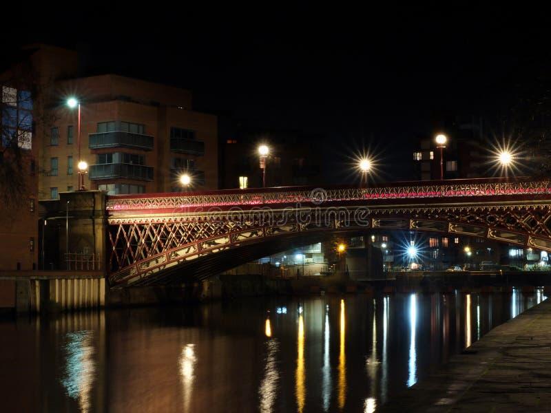 Korona punktu most krzyżuje rzecznego Aire w Leeds przy nocą z światłami i otaczającymi budynkami odbijał w wodzie obrazy royalty free
