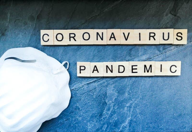 Koronavirus-Pandemietext mit Maske auf blauem Hintergrund stockfotografie
