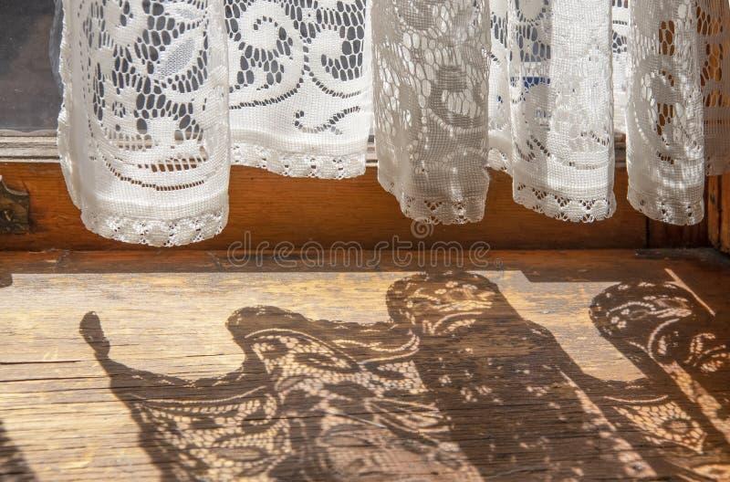 Koronkowe zasłony w starym domu - dno zasłony wiesza na Francuskim drzwi z ich cieniem ciska na starej drewnianej podłodze obrazy stock