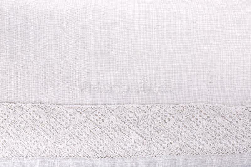 Koronkowy faborek na białej bieliźnianej tkaniny teksturze jako rabatowa rama zdjęcia royalty free