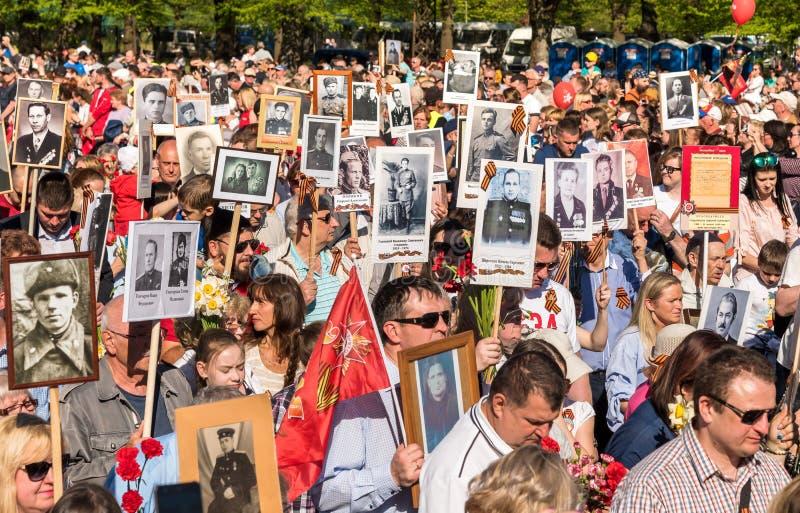 Korowód ludzie z flagami i fotografiami ich krewni w Nieśmiertelnym pułku na rocznym zwycięstwo dniu w zwycięstwo parku Ryski, fotografia royalty free