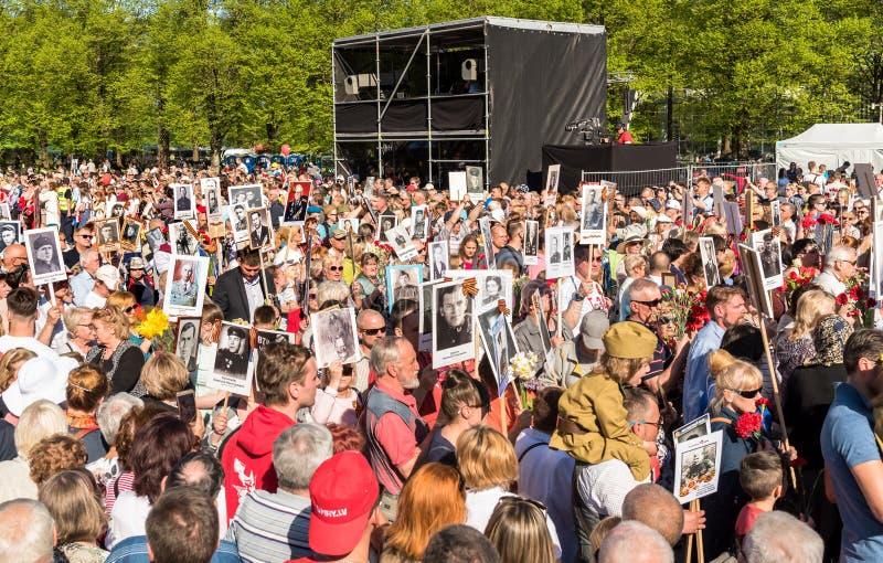 Korowód ludzie z flagami i fotografiami ich krewni w Nieśmiertelnym pułku na rocznym zwycięstwo dniu w zwycięstwo parku Ryski, zdjęcia royalty free