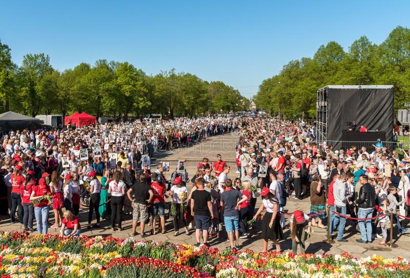Korowód ludzie z flagami i fotografiami ich krewni w Nieśmiertelnym pułku na rocznym zwycięstwo dniu w zwycięstwo parku Ryski, zdjęcie royalty free