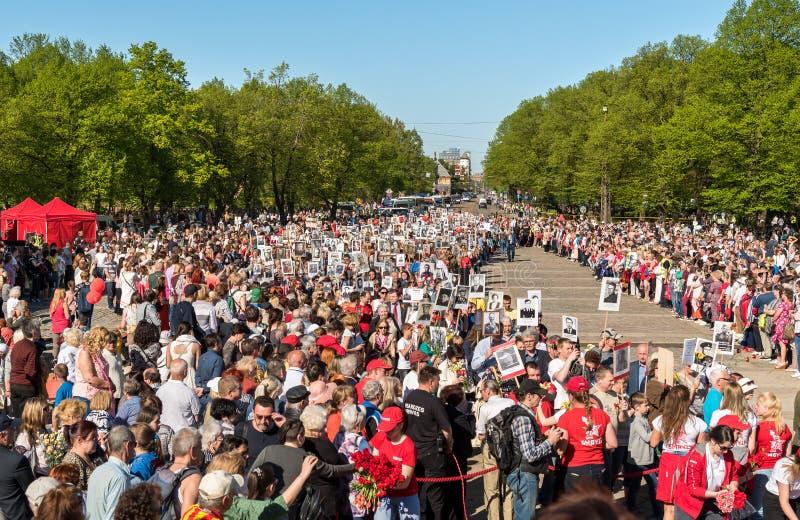 Korowód ludzie z flagami i fotografiami ich krewni w Nieśmiertelnym pułku na rocznym zwycięstwo dniu w zwycięstwo parku Ryski, obraz stock