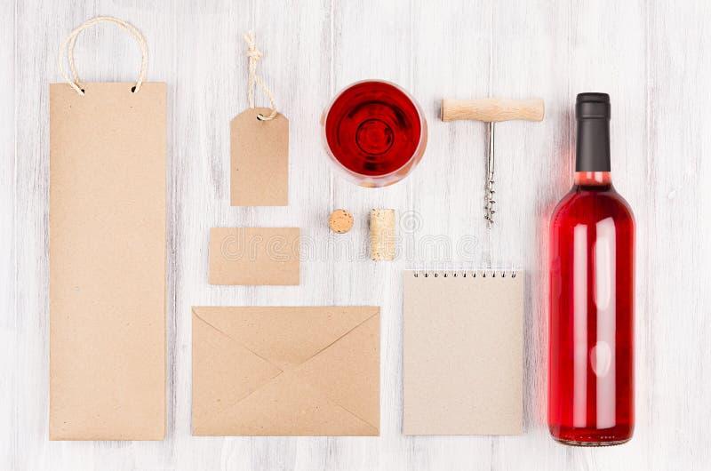 Korporacyjnej tożsamości szablon dla przemysłu winiarskiego z butelki różanym winem wineglass na miękkim białym drewnianym tle i fotografia royalty free