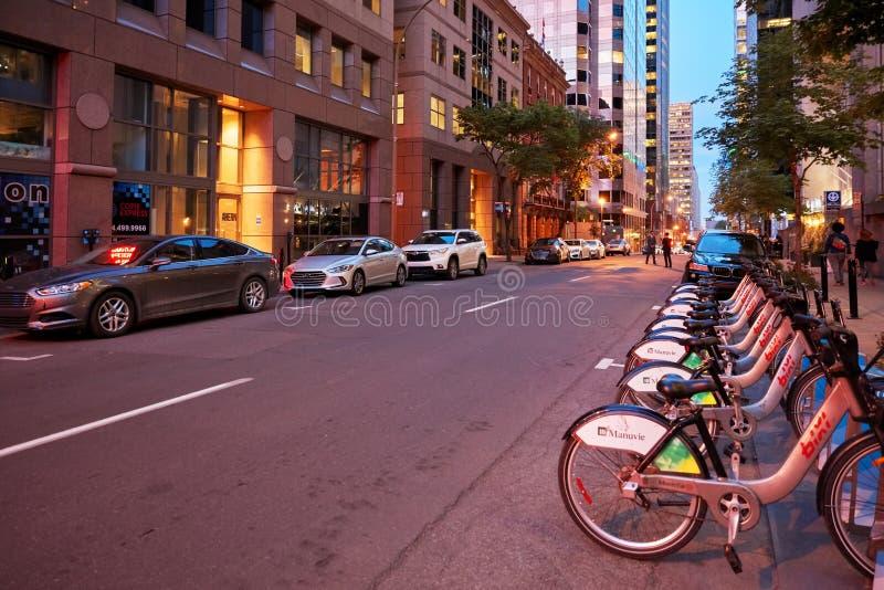 Korporacyjni budynki, miasto bicykle i ludzie na Mansfield ulicie przy zmierzchem w Montreal, Kanada obraz stock