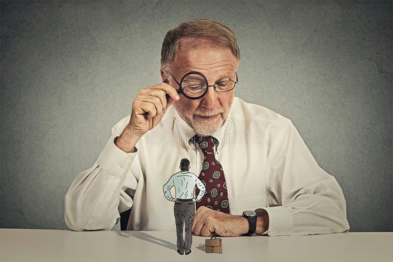 Korporacyjny biznesmen patrzeje przez powiększać przy pracownikiem - szkło obraz royalty free