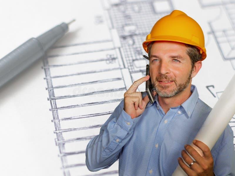Korporacyjny portret młody przemysłowego inżyniera mężczyzna lub architekt w zbawczym budowniczego hełmie opowiada na wiszącej oz obrazy stock