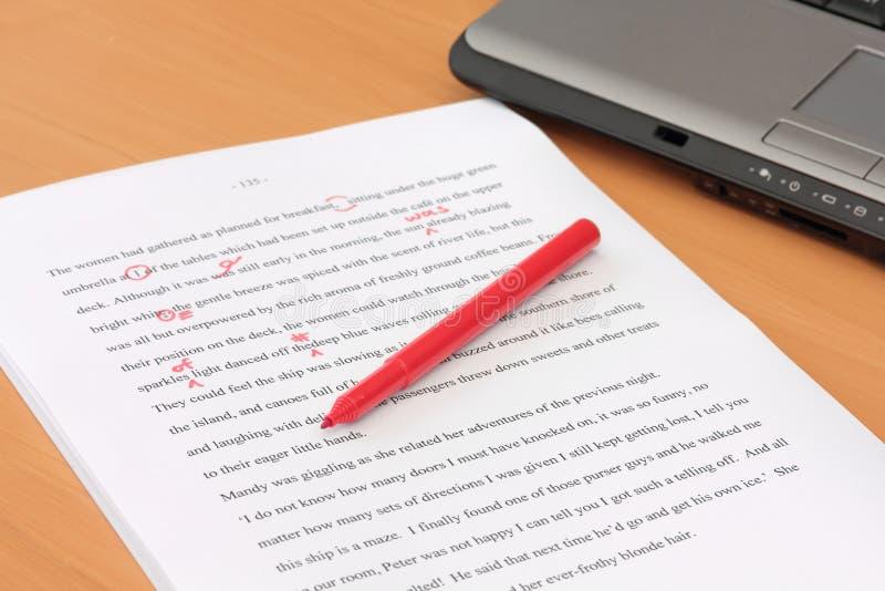 Korrekturlesen eines Manuskriptes neben Laptop stockfoto