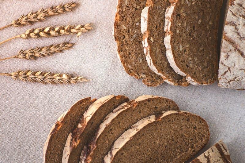 Korrel heerlijk eigengemaakt brood Stukken van brood op de scherpe raad Korreloren op een linnentafelkleed stock afbeelding