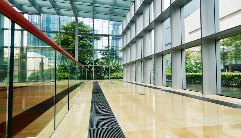 Korridor i modern glass kontorsbyggnad royaltyfria foton