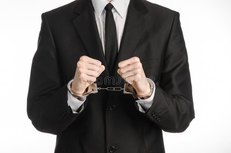 Korruption- och bestickningtema: affärsman i en svart dräkt med handbojor på hans händer på en vit bakgrund i den isolerade studi fotografering för bildbyråer