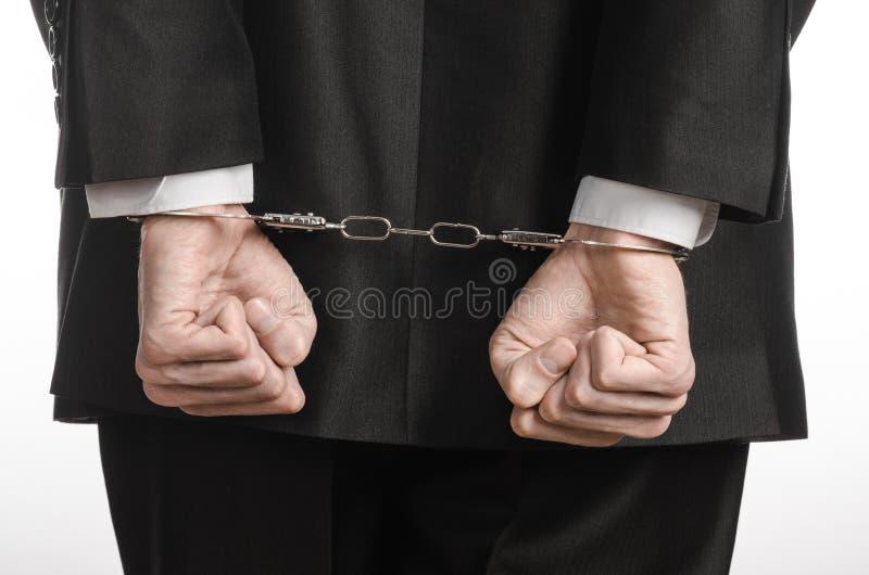 Korruption- och bestickningtema: affärsman i en svart dräkt med handbojor på hans händer på en vit bakgrund i den isolerade studi royaltyfri bild