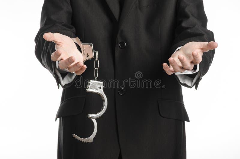 Korruption- och bestickningtema: affärsman i en svart dräkt med handbojor på hans händer på en vit bakgrund i den isolerade studi royaltyfria foton