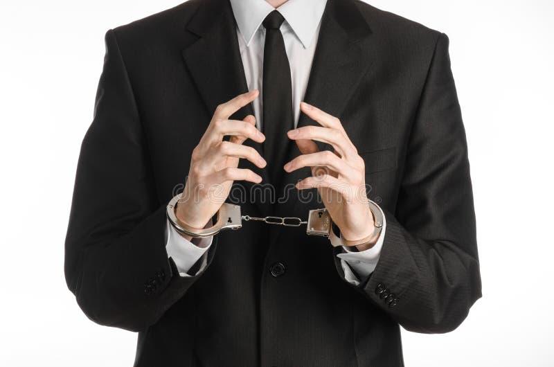 Korruption- och bestickningtema: affärsman i en svart dräkt med handbojor på hans händer på en vit bakgrund i den isolerade studi royaltyfria bilder