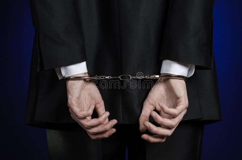 Korruption- och bestickningtema: affärsman i en svart dräkt med handbojor på hans händer på ett mörker - blå bakgrund i den isole royaltyfri foto