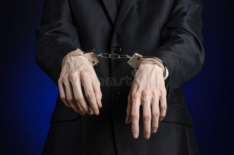 Korruption- och bestickningtema: affärsman i en svart dräkt med handbojor på hans händer på ett mörker - blå bakgrund i den isole royaltyfria foton