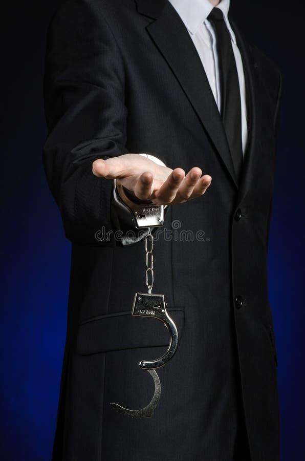 Korruption- och bestickningtema: affärsman i en svart dräkt med handbojor på hans händer på ett mörker - blå bakgrund i den isole royaltyfri fotografi