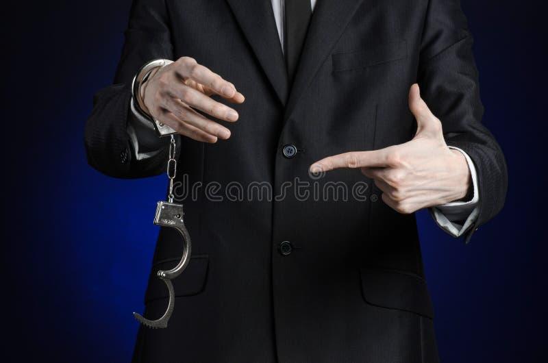 Korruption- och bestickningtema: affärsman i en svart dräkt med handbojor på hans händer på ett mörker - blå bakgrund i den isole fotografering för bildbyråer