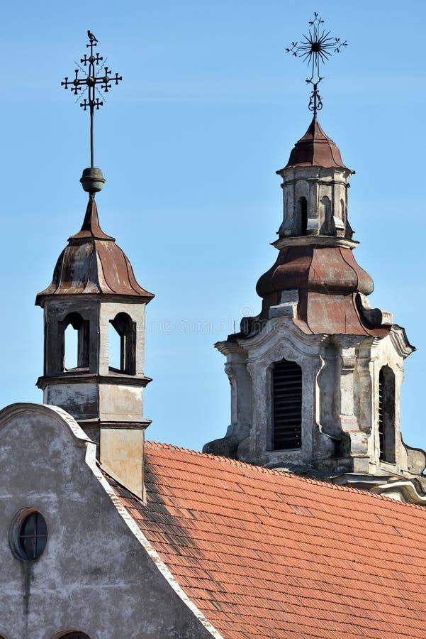 Kors av en kyrka på taket för röd tegelplatta royaltyfria foton