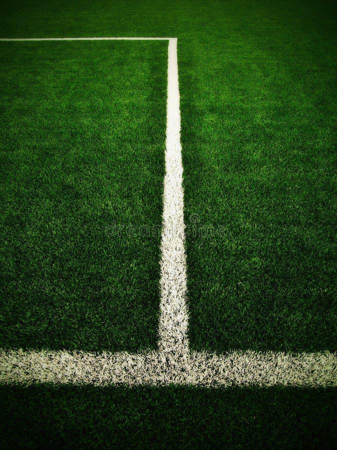 Kors av målade vita linjer på utomhus- fotbollgräs Konstgjord grön torvatextur arkivfoto