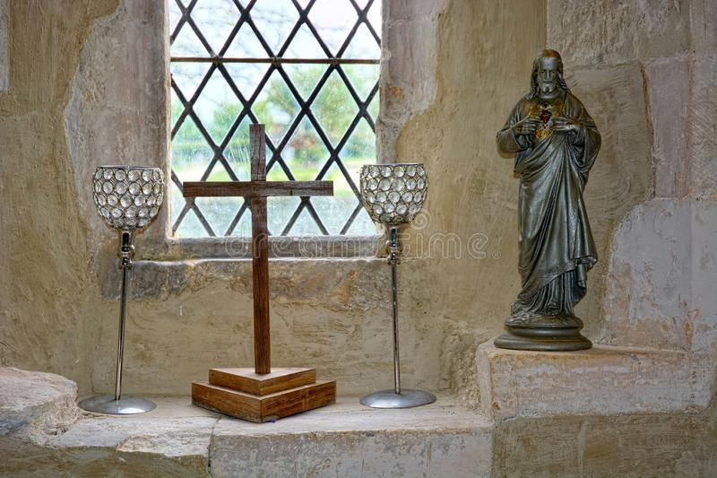 Kors, bägare och Jesus statyett arkivbilder