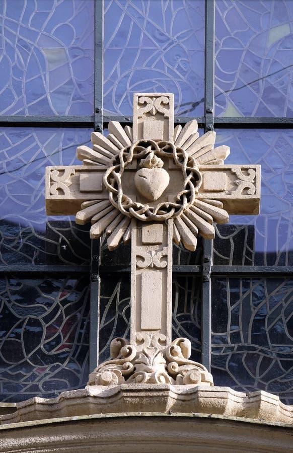 Kors på portal av församlingkyrkan av det heliga blodet i Graz arkivbild