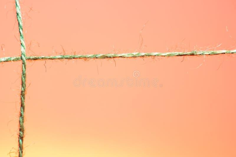 Kors-strandat rep på röd och orange bakgrund arkivfoton