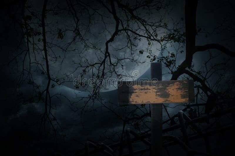 Korsa över det gamla staketet, det döda trädet, månen och molnig himmel, spöklik bac royaltyfri foto