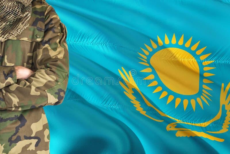 Korsad armKazakhsoldat med den nationella vinkande flaggan på bakgrund - Kasakhstan militärt tema fotografering för bildbyråer