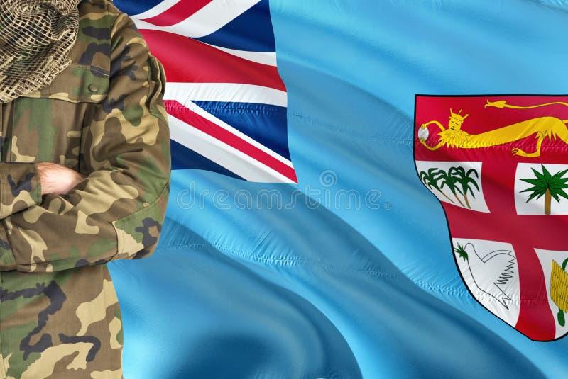 Korsad Fijian soldat för armar med den nationella vinkande flaggan på bakgrund - fijianskt militärt tema arkivfoton